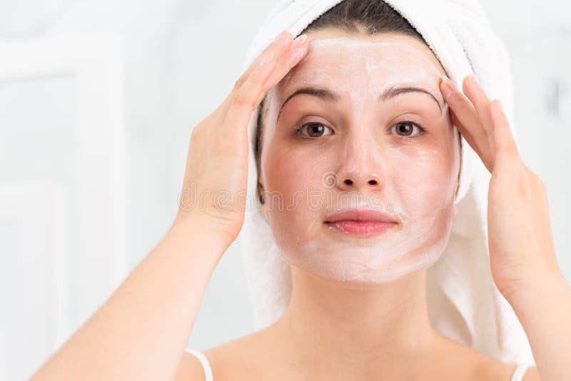 Mulher que aplica a máscara protetora fotos de stock