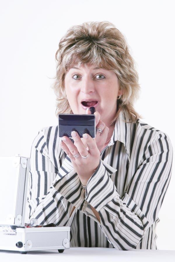 Mulher que aplica o batom fotografia de stock