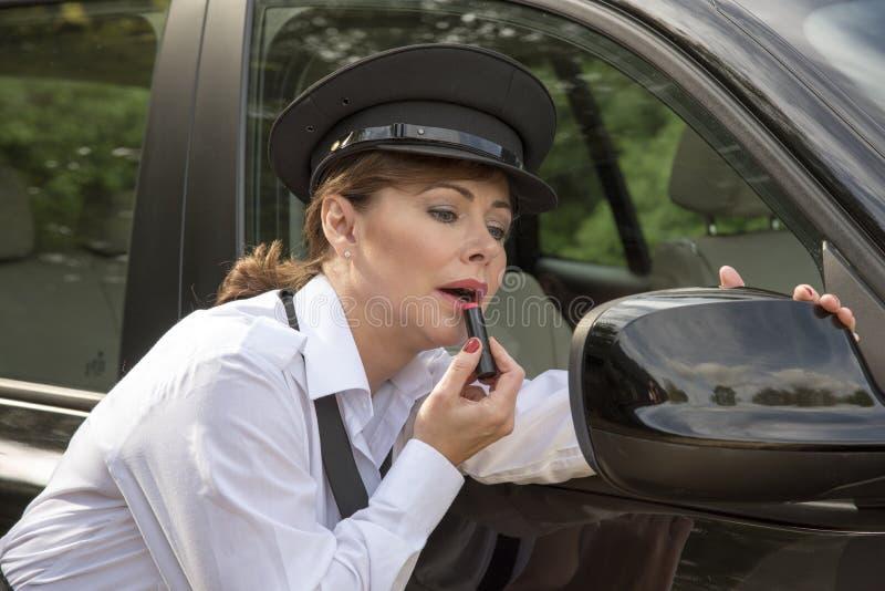 Mulher que aplica o batom que olha no espelho de asa do carro imagens de stock royalty free