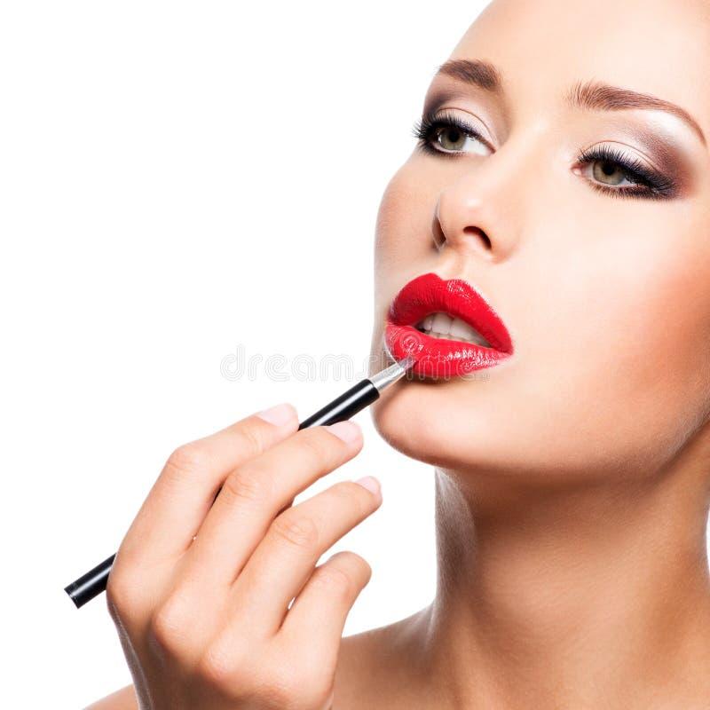 Mulher que aplica o batom vermelho com o lápis cosmético nos bordos imagem de stock royalty free