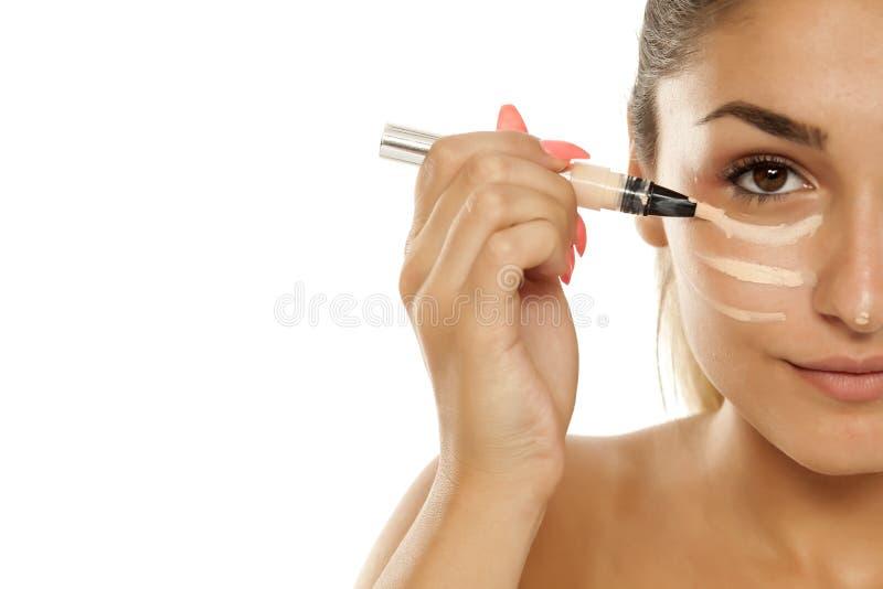Mulher que aplica o concealer foto de stock