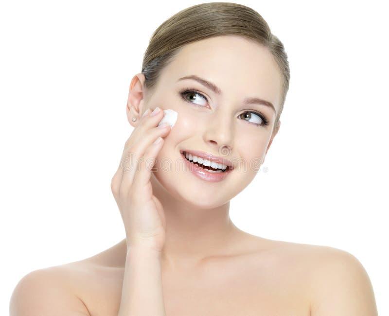 Mulher que aplica o creme cosmético na face imagens de stock