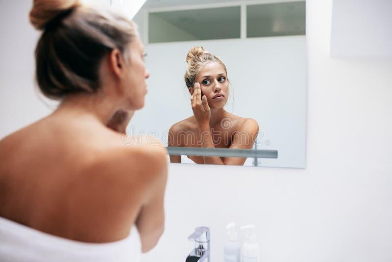 Mulher que aplica o creme cosmético na face foto de stock royalty free