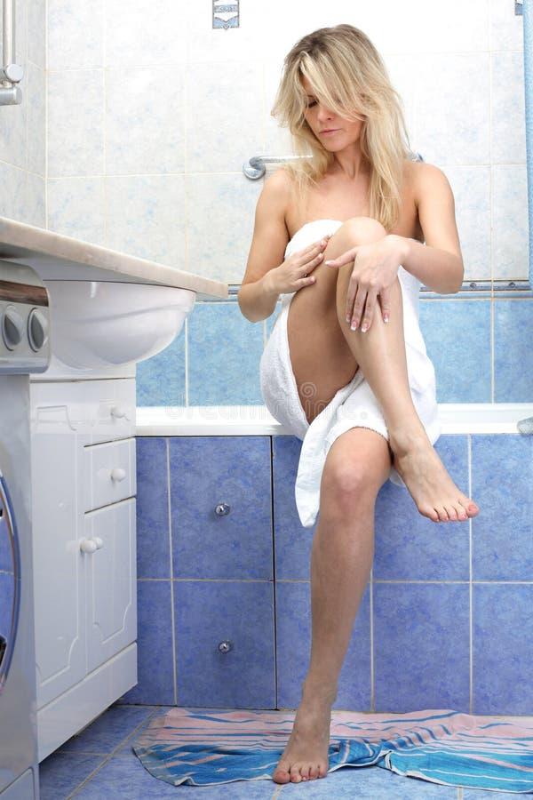 Mulher que aplica o creme cosmético no pé foto de stock royalty free