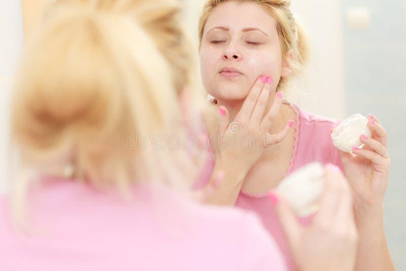 Mulher que aplica o creme de cara com seu dedo imagens de stock royalty free