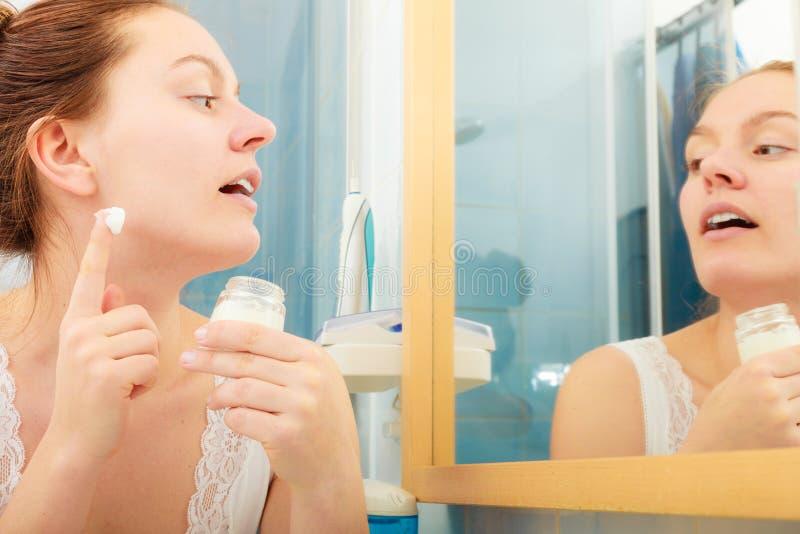 Mulher que aplica o creme de pele hidratando Skincare foto de stock