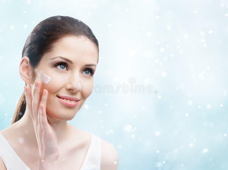 Mulher que aplica o creme em sua cara - facial do inverno foto de stock royalty free