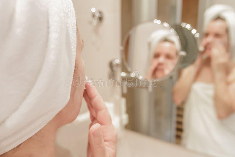 Mulher que aplica o creme em sua cara no banheiro fotografia de stock