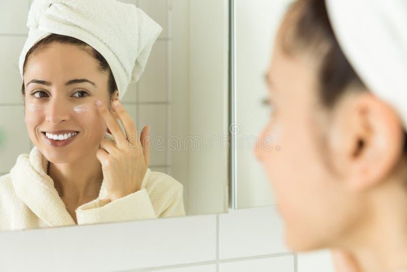 Mulher que aplica o creme hidratante a sua cara imagens de stock royalty free