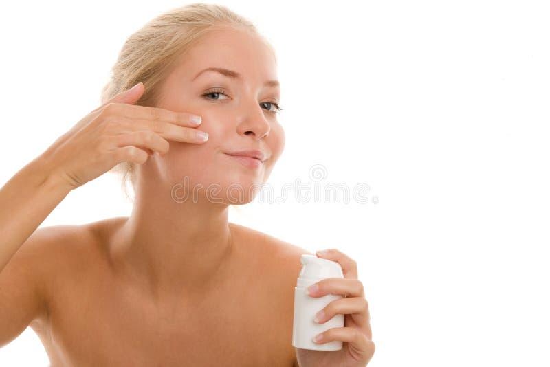 Mulher que aplica o creme na face foto de stock royalty free