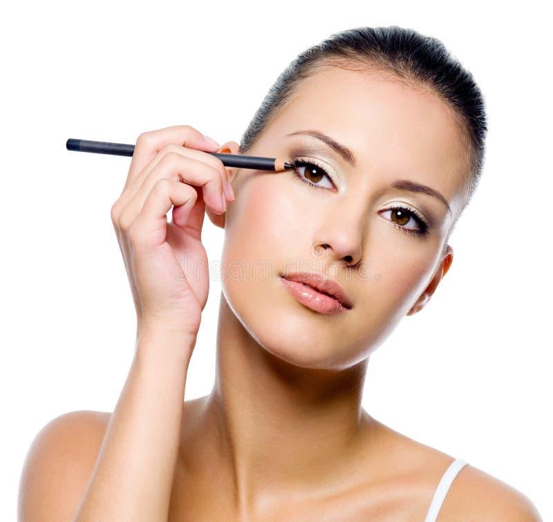 Mulher que aplica o eyeliner na pálpebra com pensil fotos de stock royalty free
