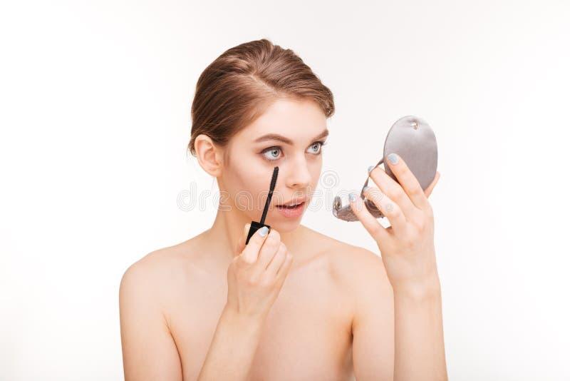 mulher que aplica o mascara em suas pestanas foto de stock