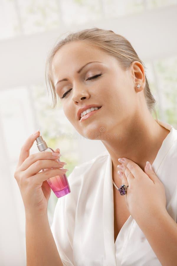 Mulher que aplica o perfume fotografia de stock