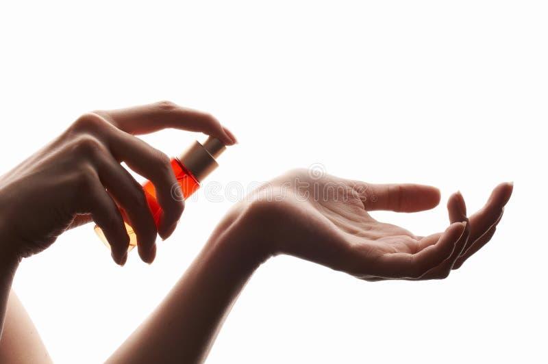 Mulher que aplica o perfume em seu pulso foto de stock