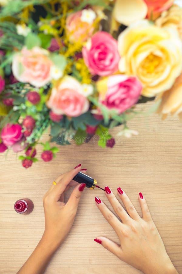 Mulher que aplica o polimento do vermelho em pregos Conceito relaxe, do cuidado e da beleza foto de stock