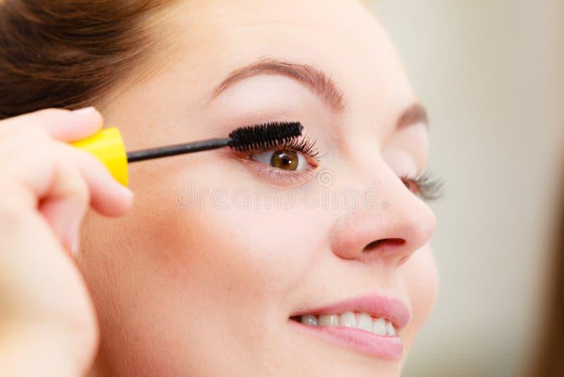 Mulher que aplica o rímel do olho roxo a suas pestanas imagens de stock