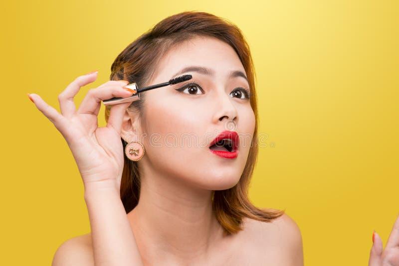 Mulher que aplica o rímel preto nas pestanas com escova da composição sobre foto de stock royalty free