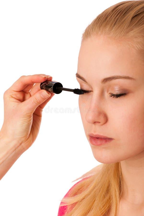 Mulher que aplica o rímel preto nas pestanas, fazendo a composição foto de stock royalty free