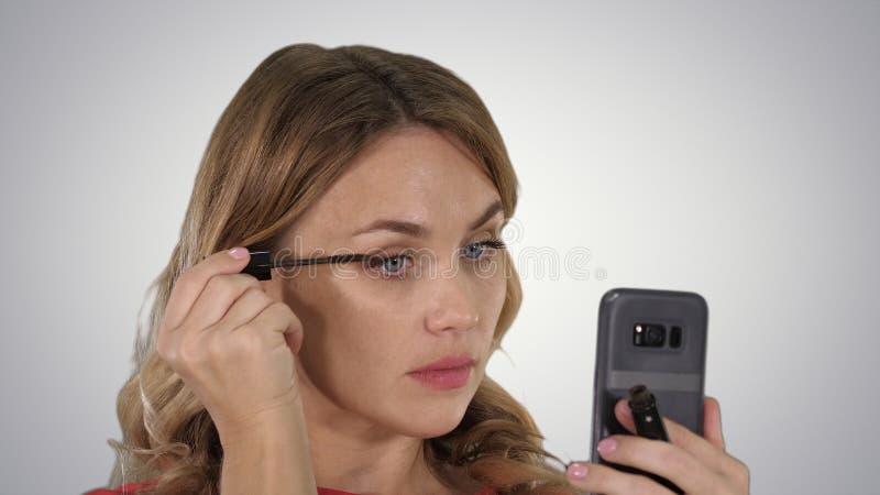 Mulher que aplica o rímel preto nas pestanas que olham em seu telefone no fundo do inclinação imagens de stock royalty free