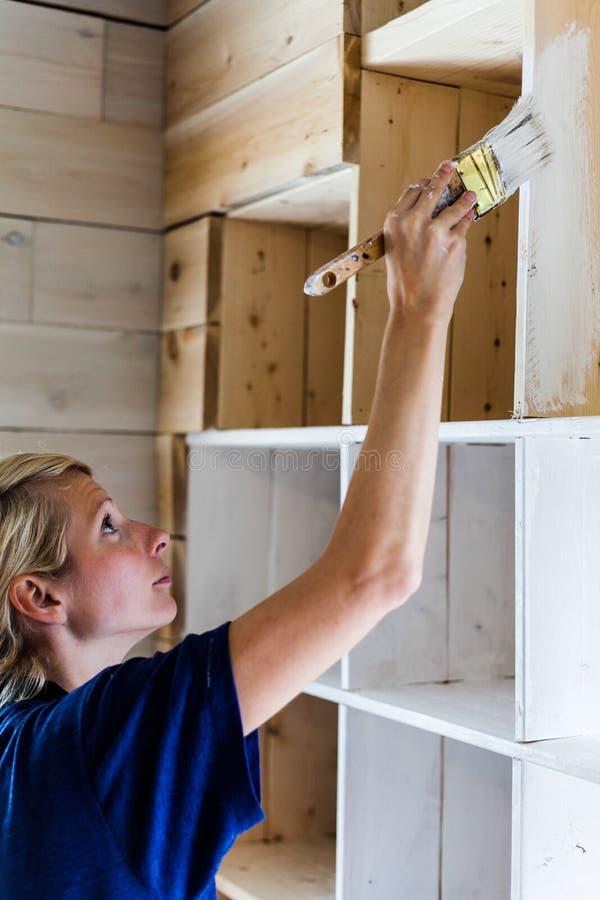 Mulher que aplica a primeira camada de pintura em uma biblioteca de madeira imagens de stock
