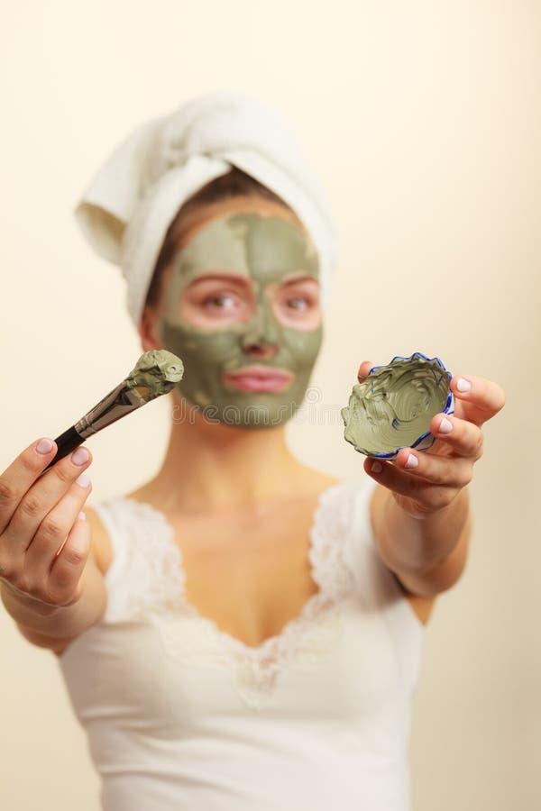Mulher que aplica-se com máscara da lama da argila da escova a sua cara fotografia de stock royalty free