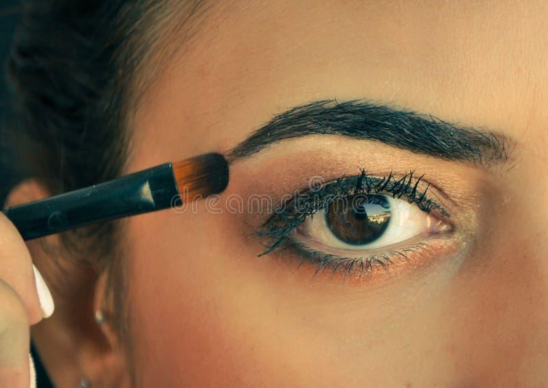 Mulher que aplica a sombra em seus olhos imagem de stock