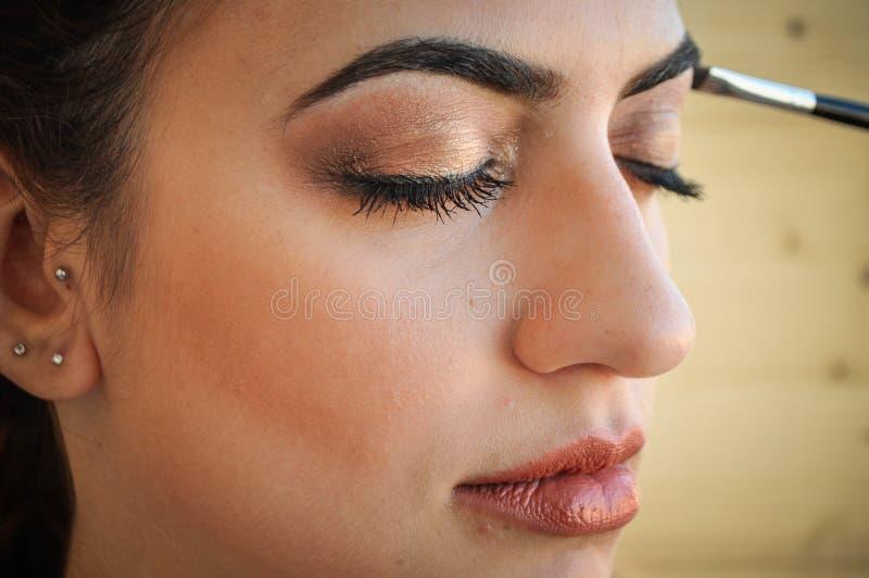 Mulher que aplica a sombra em seus olhos imagens de stock royalty free