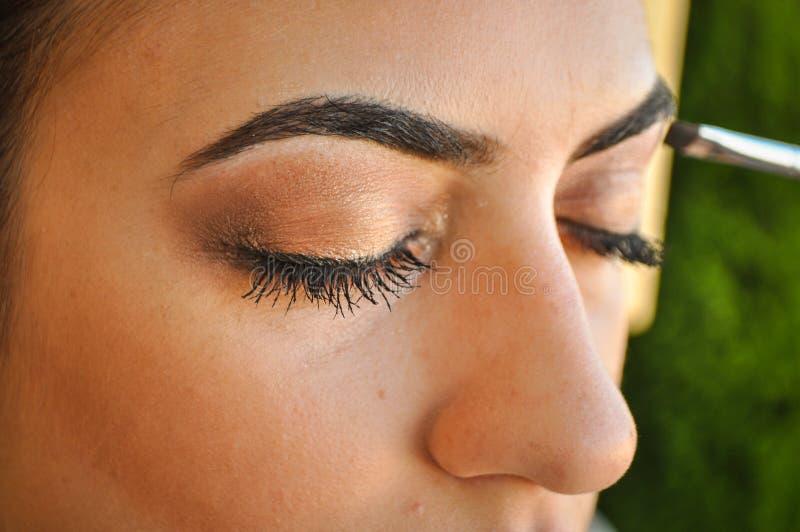 Mulher que aplica a sombra em seus olhos foto de stock