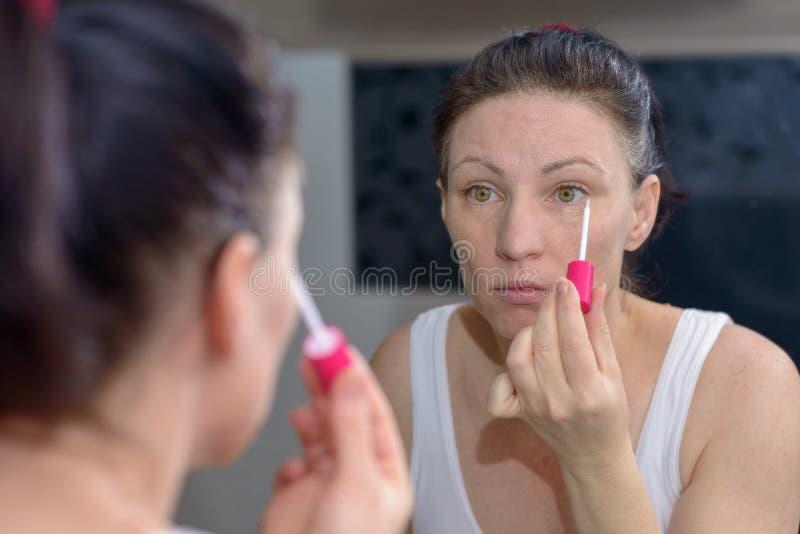Mulher que aplica um brilho pastel moderno do bordo fotos de stock royalty free