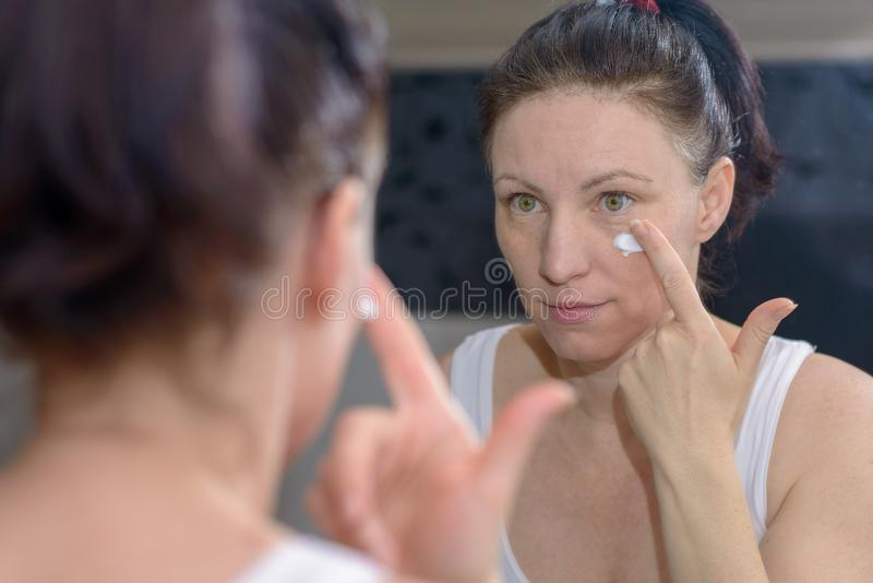Mulher que aplica um creme hidratando a seu mordente fotografia de stock royalty free