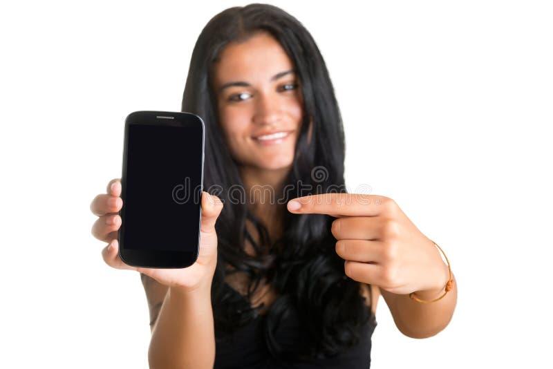 Mulher que aponta em um telefone celular imagem de stock