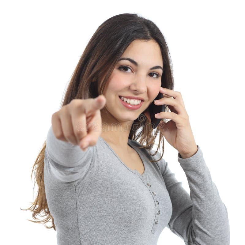 Mulher que aponta na câmera que chama o telefone celular fotografia de stock