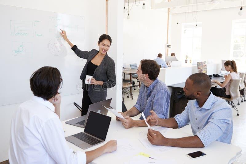Mulher que aponta no whiteboard em uma reunião em um escritório ocupado fotografia de stock royalty free