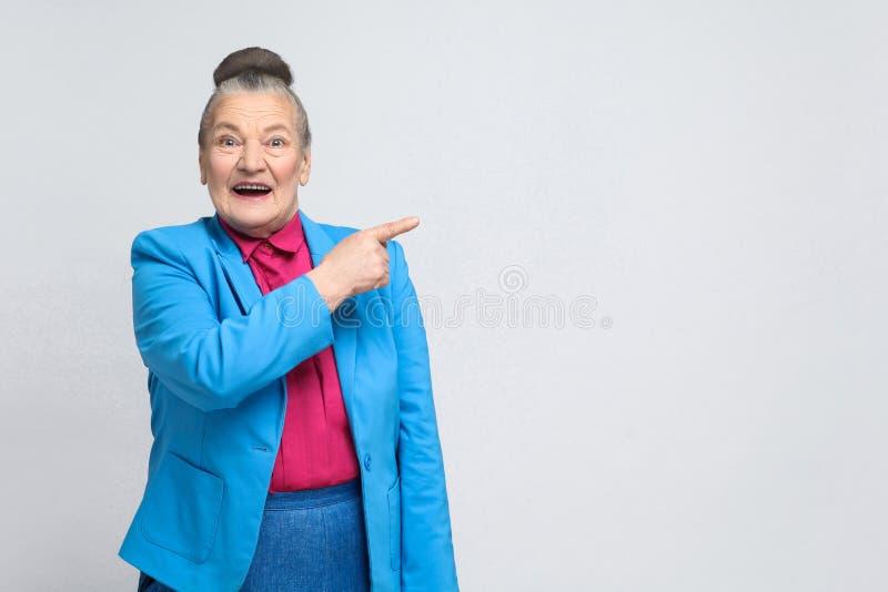 Mulher que aponta o dedo no espaço da cópia e no sorriso toothy foto de stock royalty free