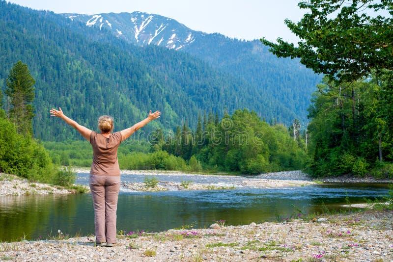 Mulher que aprecia as vistas do rio, da floresta e das montanhas nevado de Snezhnaya fotos de stock royalty free