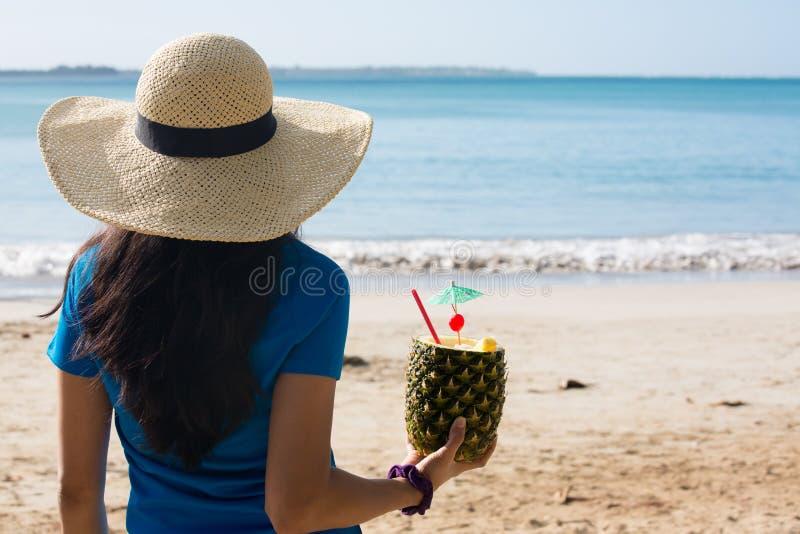 Mulher que aprecia a bebida do abacaxi no dia ensolarado imagem de stock