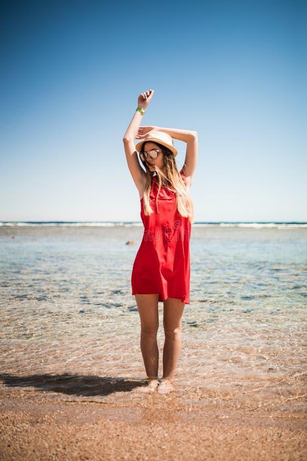 A mulher que aprecia a liberdade em uma costa do oceano com mãos aumentou no fundo da água Vocação do verão imagem de stock