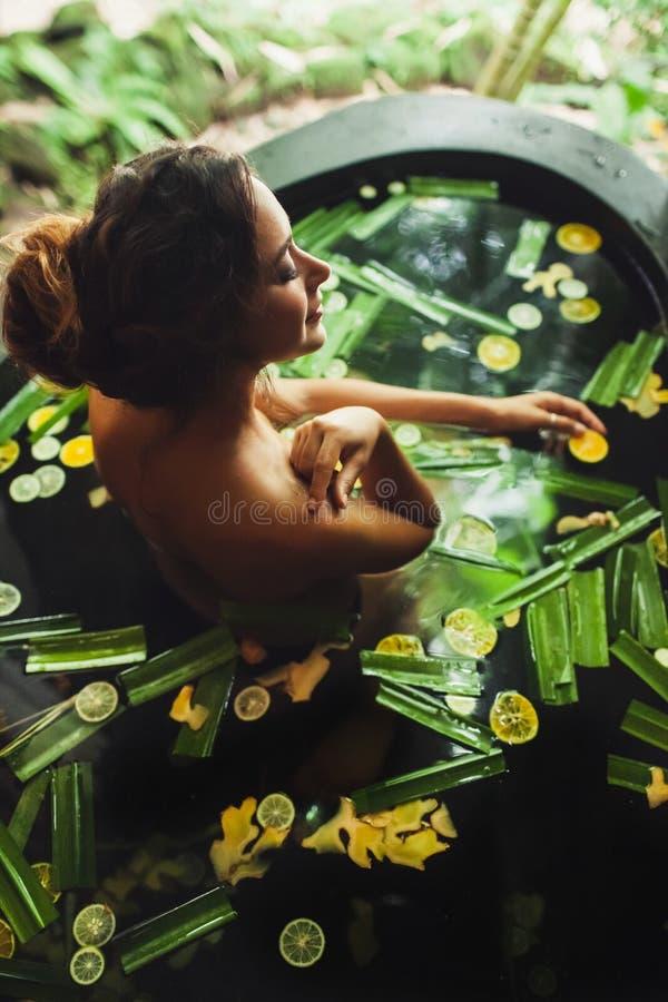 Mulher que aprecia na banheira tropical exterior dos termas imagem de stock royalty free