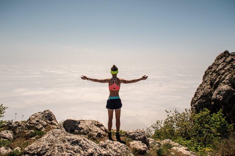 Mulher que aprecia a natureza nas montanhas e que olha no céu com mãos levantadas foto de stock royalty free