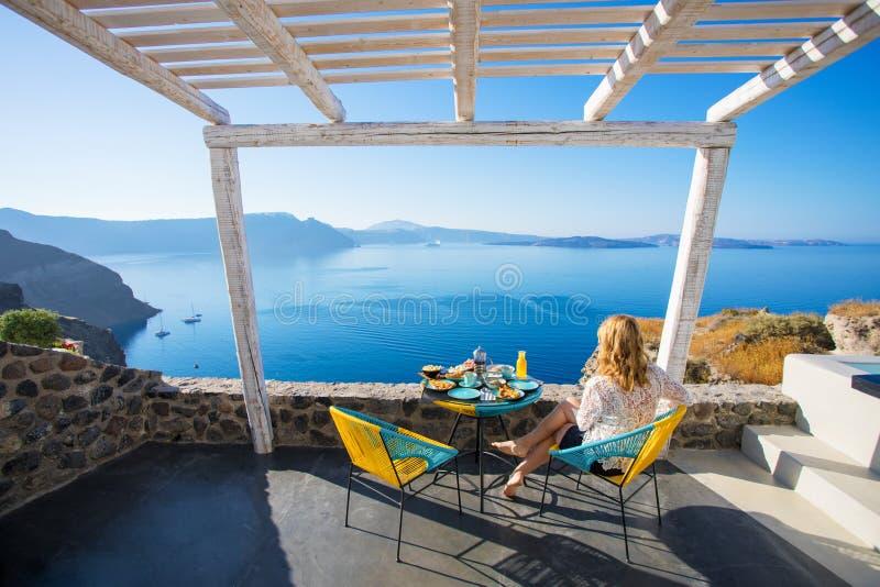 Mulher que aprecia o café da manhã com vista bonita sobre Santorini fotos de stock