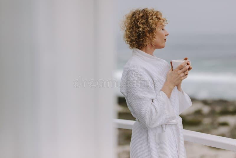Mulher que aprecia o café que está no balcão de uma casa de praia imagens de stock