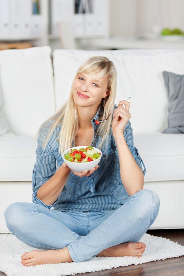 Mulher que aprecia a salada de fruto fotografia de stock royalty free