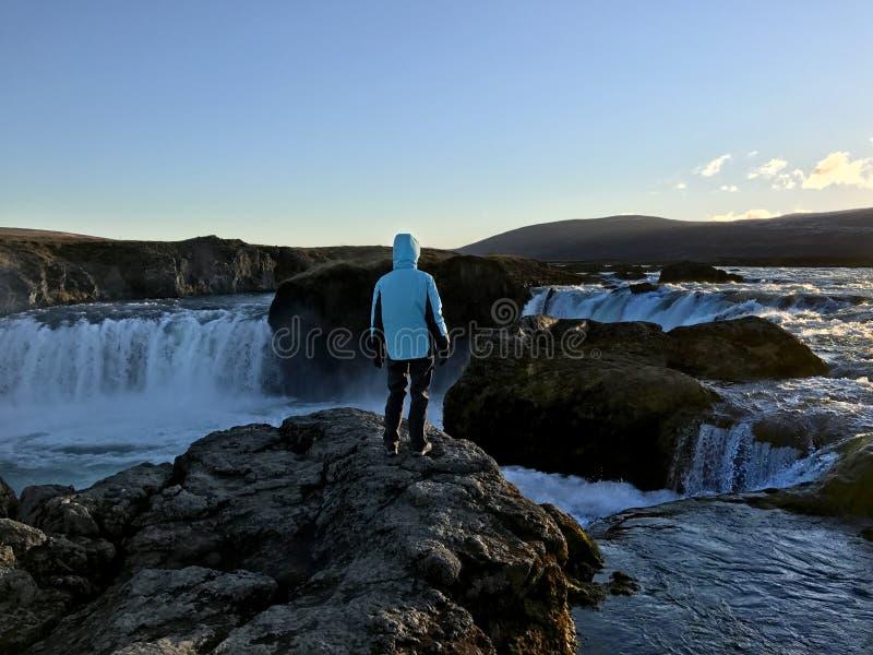 Mulher que aprecia a vista da cachoeira de Godafoss em Islândia foto de stock royalty free