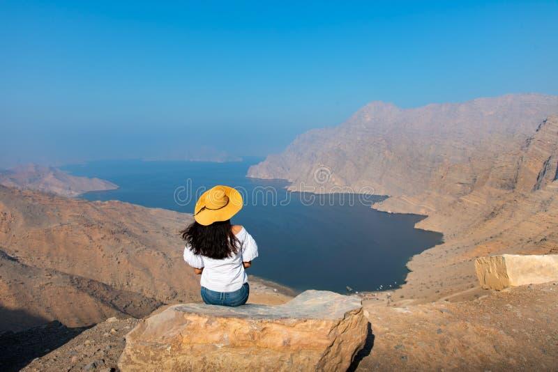 Mulher que aprecia a vista sobre o fiorde Khor Najd em Omã foto de stock