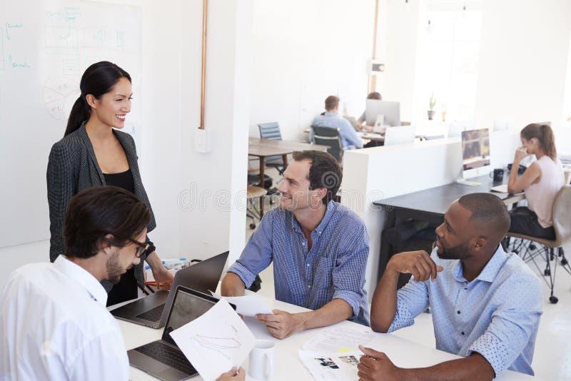 Mulher que apresenta uma reunião do clique em um escritório de plano aberto imagem de stock royalty free
