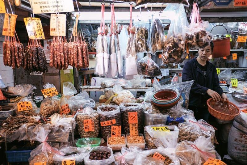 Mulher que arranja alimentos frescos no mercado local imagem de stock