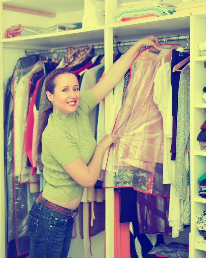Mulher que arranja a roupa no vestuário fotografia de stock royalty free