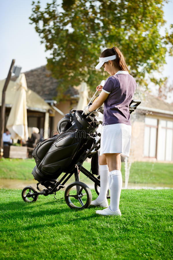 Mulher que arranja seu equipamento de golfe imagem de stock royalty free