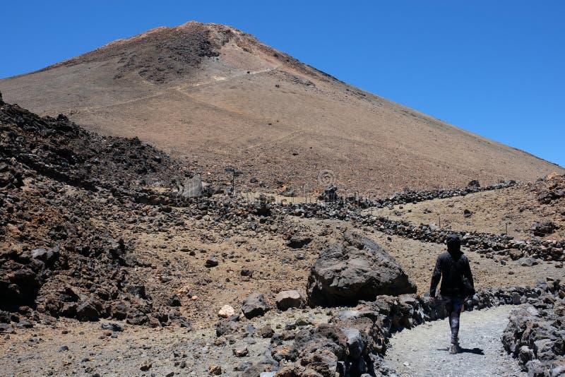 Mulher que ascensão o pico de montanha de Teide em um volca seco e rochoso imagens de stock royalty free