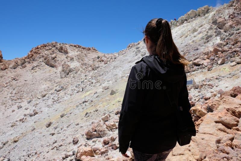 Mulher que ascensão o pico de montanha de Teide em uma paisagem vulcânica seca e rochosa imagem de stock royalty free